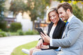 Business Couple Using Digital Tablet On Park Bench Royalty Free Stock Photo