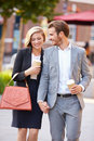 Business couple walking through park with takeaway coffee holding hands smiling Royalty Free Stock Image