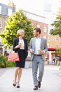 Business couple walking through park with takeaway coffee smiling at each other Royalty Free Stock Images
