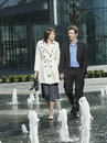 Business couple walking between water jets of fountain full length happy young Stock Images