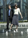 Business couple walking between water jets of fountain full length happy young Royalty Free Stock Photography
