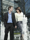 Business couple walking between water jets of fountain happy young Stock Photo