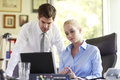 Business couple working on laptop young businesspeople in office shallow focus Stock Photography