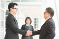 Business deal asian businessmen handshaking senior ceo hand shake with young executive modern office building architecture Royalty Free Stock Photography
