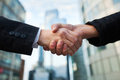 Business deal handshake on the office buildings background Royalty Free Stock Images