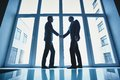 Business deal silhouettes of two successful businessmen handshaking after striking Royalty Free Stock Photography