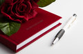 Business diary with rose and pen flower on the closed Royalty Free Stock Photos