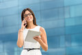 Business executive with tablet and phone woman holding pc computer calling on cell outside corporate building caucasian hispanic Royalty Free Stock Photo