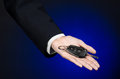 Business and gift theme: car salesman in a black suit holds the keys to a new car on a dark blue background in studio Royalty Free Stock Photo