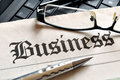Business glasses and ball pen on newspaper headline Royalty Free Stock Images