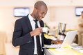 Business on the go cheerful young african man in formalwear using his laptop while standing at bar Royalty Free Stock Photos