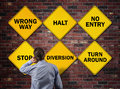 Business going the wrong way businessman in front of a brick wall with stop halt no entry diversion and turn around road signs Stock Photography