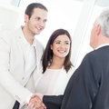 Business handshake a married couple shaking hands with their financial advisor Royalty Free Stock Photography