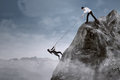 Business help to overcome adversity portrait of businessman his partner climb the cliff by pulling her with a rope Stock Photos