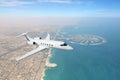 Business jet airplane flying over Dubai city and sea coastline Royalty Free Stock Photo