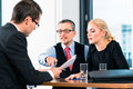 Business job interview with candidate and hr young men in an hands over his application papers to the boss his female assistant in Royalty Free Stock Photography