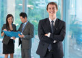 Business leader portrait of a young handsome smiling and looking at camera on the foreground Royalty Free Stock Image