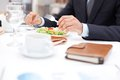 At business lunch close up of businessman hands holding knife and fork over vegetable salad during Stock Photo
