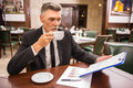 Business lunch senior businessman in suit sitting in cafe and drinking coffee Stock Photo