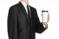 Business lunches coffee theme: businessman in a black suit holding a white blank paper cup of coffee with a brown plastic cap isol Royalty Free Stock Photo