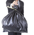 A business man arm holding a black bag of trash concept bad debt Royalty Free Stock Photo