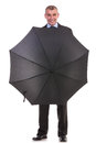 Business man behind an opened umbrella full length picture of a standing with his and smiling for the camera on a white background Royalty Free Stock Images