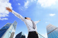 Business man carefree outstretched arms with sky and city background asian Stock Photo