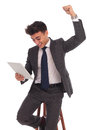 Business man celebrating good news he reads on this tablet Royalty Free Stock Photo