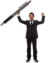 Business man celebrating holding a huge pen with arms up Stock Image