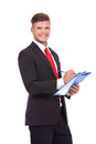 Business man with clipboard young writing something on his while looking at the camera a big smile on his face isolated on white Royalty Free Stock Image