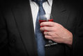 Business man closeup view of inebriated in suit and tie holding wine glass Stock Image