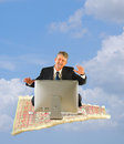 Business man with computer on a magic carpet ride Royalty Free Stock Photo