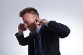 Business man covers his ears young plugging with fingers and closing eyes while screaming on a light gray studio background Royalty Free Stock Photography