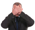 Business man covers his eyes covering with palms on a white background Stock Image
