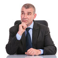 Business man at desk looks away pensively sitting the and looking while holding his hand his chin on a white background Royalty Free Stock Image