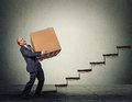 Business man with a difficult task middle aged climbing up staircase big heavy box Royalty Free Stock Image