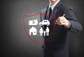 Business man drawing shield protecting family house car money insurance concept Stock Images