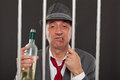 Business man drunk in jail holding a wine bottle Royalty Free Stock Photography