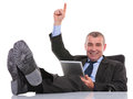 Business man with feet on desk holds his tablet and points up sitting at the office the while holding a pointing a smile for the Stock Photos