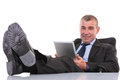 Business man with feet on desk holds his tablet standing legs the while holding and looking into the camera a smile face a Stock Image