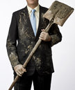 Business man getting dirty well dressed holding a shovel with clothes relationship between blue collar and white collar workers Royalty Free Stock Image