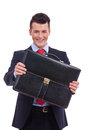 Business man giving his briefcase Stock Photos