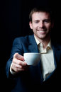 Business man giving you a coffee cup smiling focus on Stock Photo