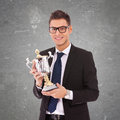 Business man  with glasses holding a big trophy Royalty Free Stock Photo