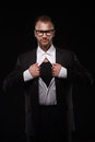 Business man in glasses tearing off his shirt on black background Royalty Free Stock Photo