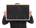 Business man hides behind blackboard holding a in front of his face on a white background Royalty Free Stock Images