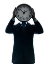Business man holding clock silhouette one caucasian businessman in studio isolated on white background Stock Photo