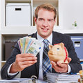 Business man holding euro money happy in his office bills and a piggy bank Stock Photo