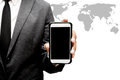 Business man holding smart phone with world map graphic Royalty Free Stock Photo