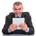 Business man holding a tablet at his desk while sitting the office and smiling for the camera on white background Royalty Free Stock Images